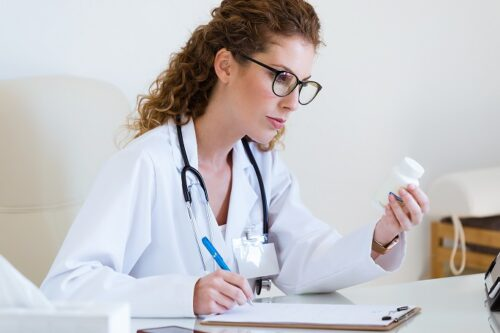 Portrait of beautiful female pharmacist holding jar of pills in hands in the office.